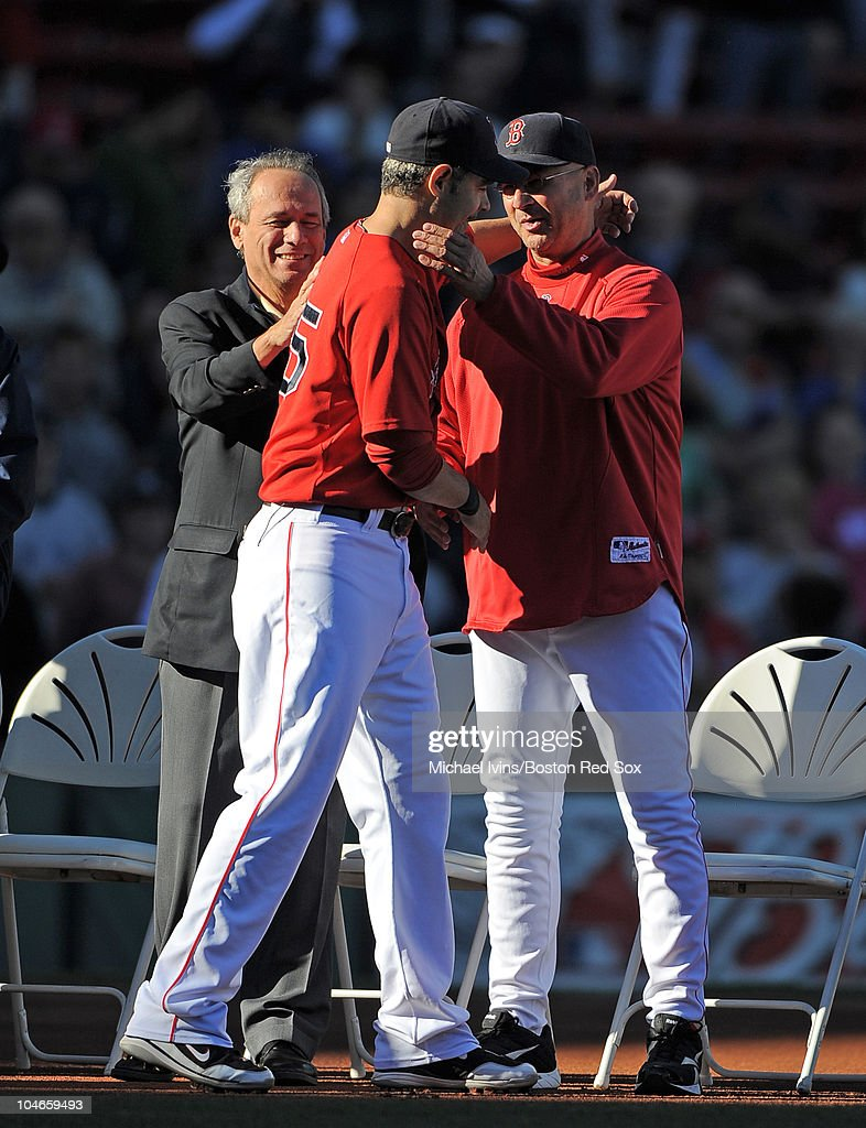 Mike Lowell of the Boston Red Sox gets a pat on the back from Red Sox CEO Larry Lucchino and a hug from manager Terry Francona while being honored...