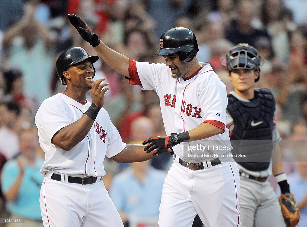 Mike Lowell of the Boston Red Sox is greeted at home plate by Adrian Beltre after hitting a tworun home run on the first pitch he saw against the...