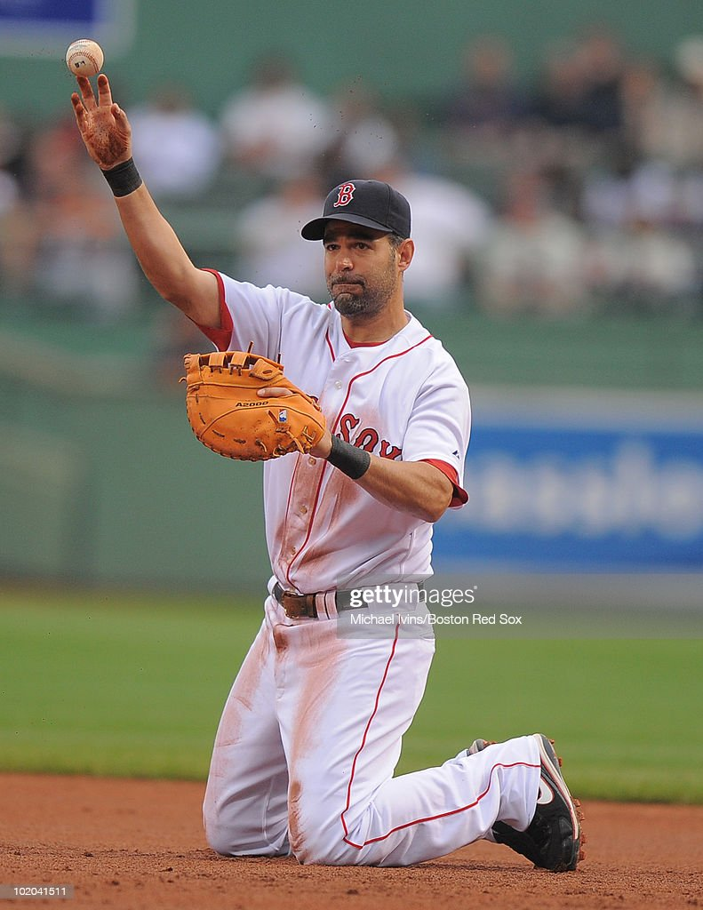 Mike Lowell of the Boston Red Sox throws to first base from his knees after diving to stop a ground ball against the Philadelphia Phillies in the...