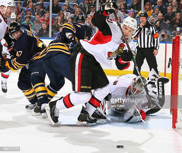 Mike Lundin and Robin Lehner of the Ottawa Senators look to clear the puck as Steve Ott and Nathan Gerbe of the Buffalo Sabres keep a close eye on...