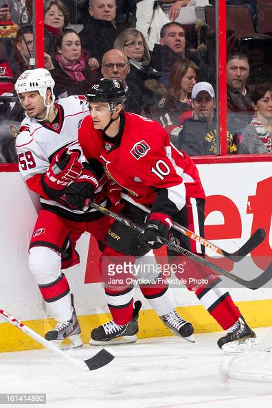 Mike Lundin of the Ottawa Senators checks Chad LaRose of the Carolina Hurricanes along the boards during an NHL game at Scotiabank Place on February...