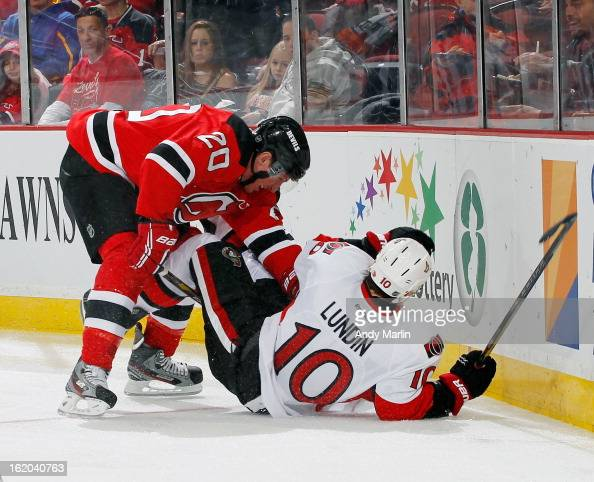 Mike Lundin of the Ottawa Senators falls to the ice after being checked by Ryan Carter of the New Jersey Devils during the game at the Prudential...