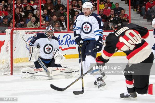 Mike Lundin of the Ottawa Senators fires the puck against Ron Hainsey and Al Montoya of the Winnipeg Jets during an NHL game at Scotiabank Place on...