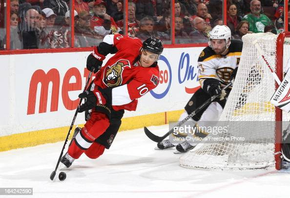 Mike Lundin of the Ottawa Senators loses his footing as he falls to the ice while being chased by Patrice Bergeron of the Boston Bruins during an NHL...