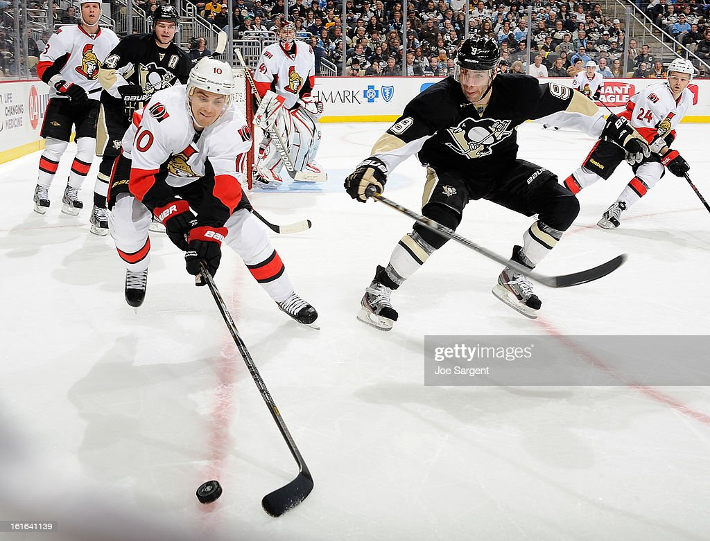Mike Lundin #10 of the Ottawa Senators reaches for the loose puck in front of Pascal Dupuis #9 of the Pittsburgh Penguins on February 13, 2013 at Consol Energy Center in Pittsburgh, Pennsylvania.