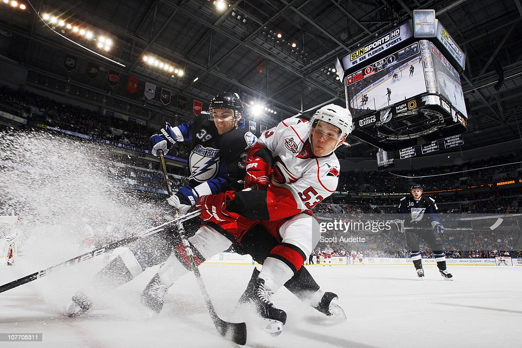 Mike Lundin of the Tampa Bay Lightning battles for the puck against Jeff Skinner of the Carolina Hurricanes at the St Pete Times Forum on December 20...