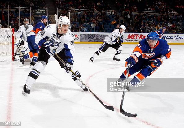 Mike Lundin of the Tampa Bay Lightning tries to control the puck as he's being pursued by Frans Nielsen of the New York Islanders on November 17 2010...