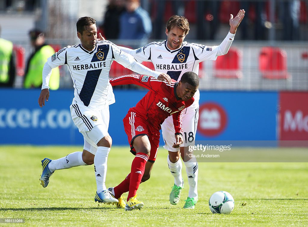 Mike Magee #18 and Marcelo Sarvas #8 of the Los Angeles Galaxy play against <a gi-track='captionPersonalityLinkClicked' href=/galleries/search?phrase=Robert+Earnshaw&family=editorial&specificpeople=208190 ng-click='$event.stopPropagation()'>Robert Earnshaw</a> #10 of the Toronto FC in an MLS game on March 30, 2013 at BMO Field in Toronto, Ontario, Canada. The Los Angeles Galaxy and Toronto FC played to a 2-2 tie.