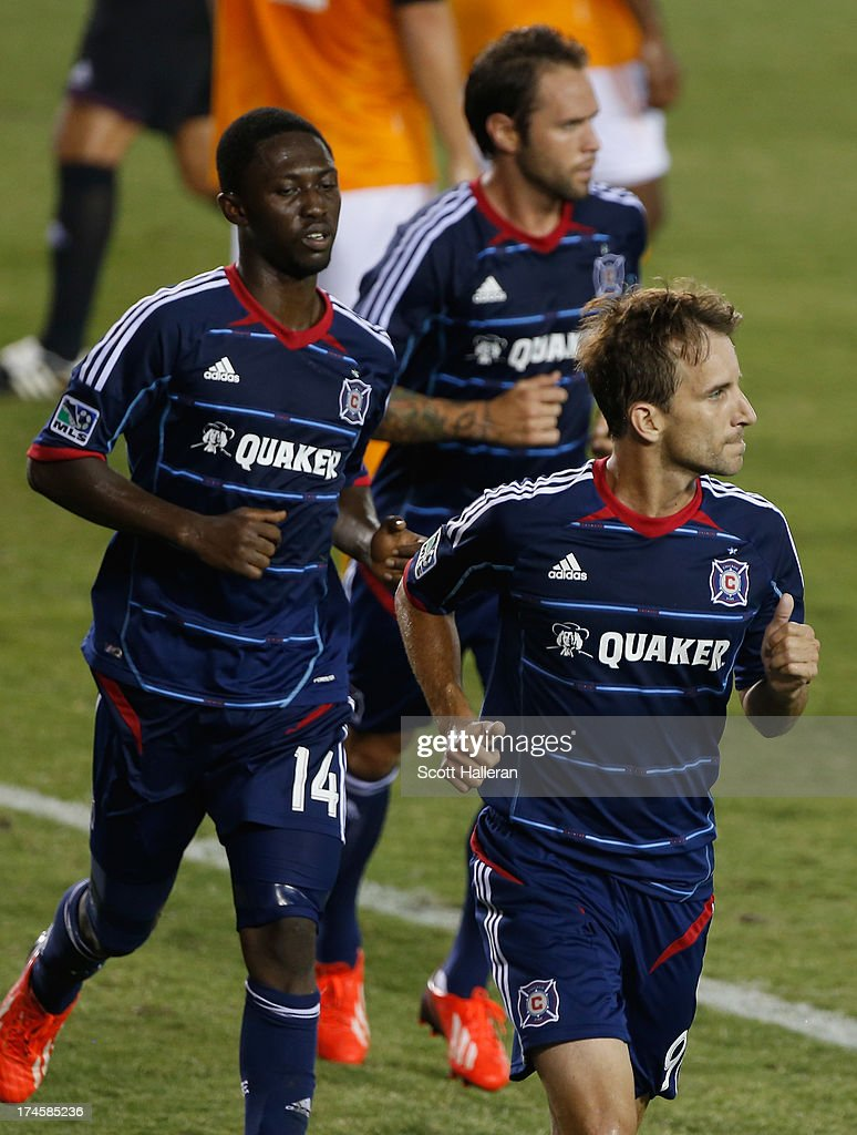 Mike Magee #9 (R) and Patrick Nyarko #14 (L) of the Chicago Fire celebrate after Magee scored a second half goal against the Houston Dynamo at BBVA Compass Stadium on July 27, 2013 in Houston, Texas.