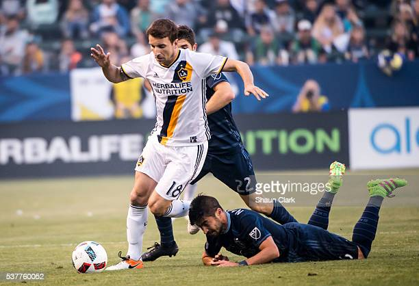 Mike Magee of Los Angeles Galaxy breaks past Paulo Nagamura of Sporting Kansas City during Los Angeles Galaxy's MLS match against Sporting KC at the...