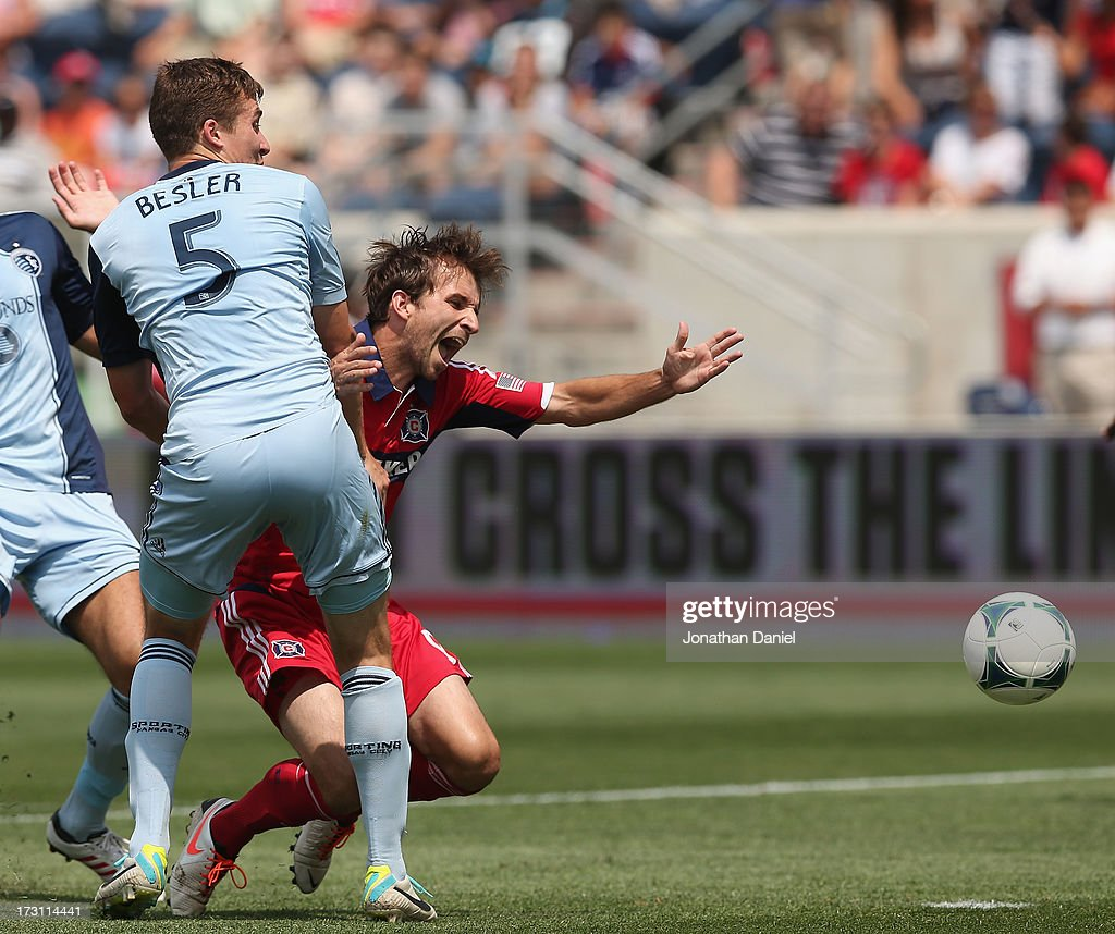 Mike Magee of the Chicago Fire is hit while trying to shoot by Matt Besler of Sporting Kansas City during an MLS match at Toyota Park on July 7 2013...