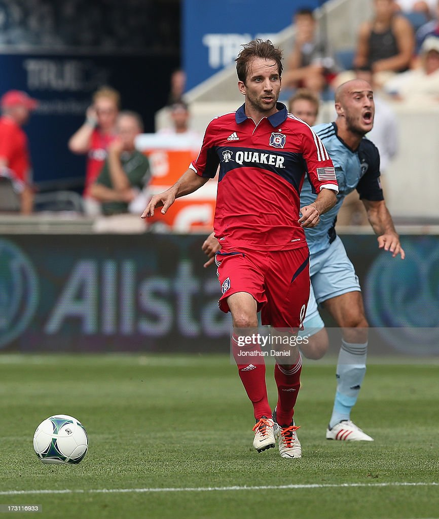 Mike Magee of the Chicago Fire scores a first half goal past Aurelien Collin of Sporting Kansas City during an MLS match at Toyota Park on July 7...