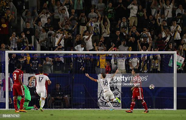 Mike Magee of the Los Angeles Galaxy celebrates after converting a penalty kick as Getterson and Michael Barrios of FC Dallas look on in the second...