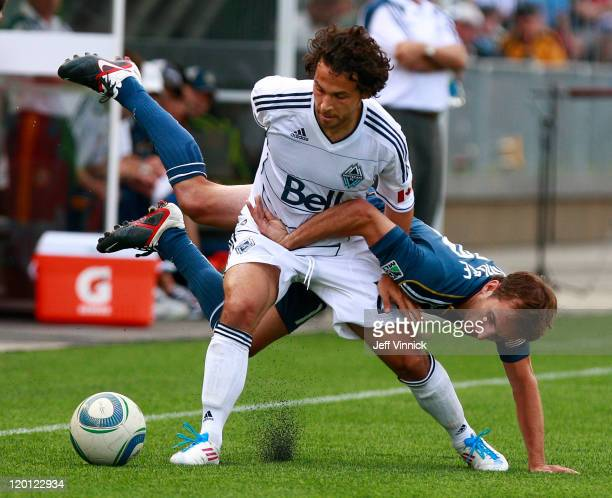 Mike Magee of the Los Angeles Galaxy slips over the back of Davide Chiumiento of the Vancouver Whitecaps FC during their MLS game July 30 2011 at...