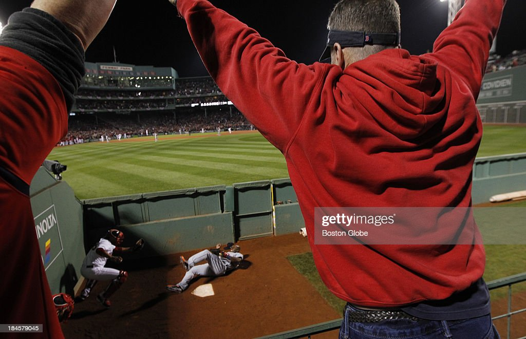 Mike McDonald, of Medfield, celebrates as Torii Hunter lands in the Red Sox bullpen chasing David Ortiz's grand slam to tie the game in the eighth inning. The Boston Red Sox hosted the Detroit Tigers in Game Two of the American League Championship Series at Fenway Park.