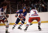 Mike McEwen of the New York Islanders is defended by Barry Beck of the New York Rangers during an 1981 Stanley Cup Semi Finals game in May 1981 at...