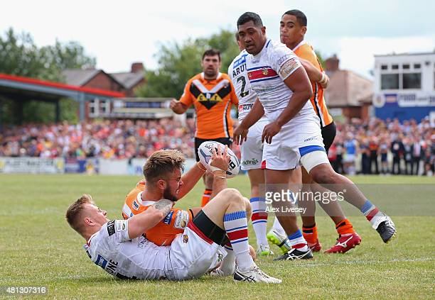 Mike McMeeken of Castleford Tigers holds off a tackle from Tom Johnstone of Wakefield Trinity Wildcats as he scores their third try during the First...