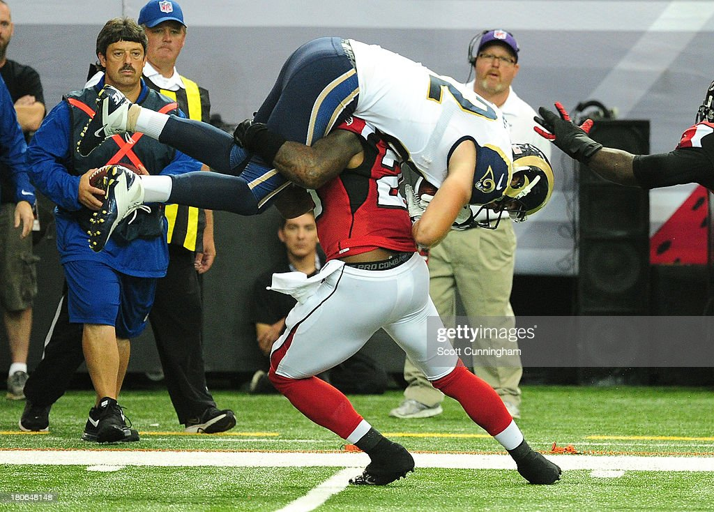 Mike McNeill #82 of the St. Louis Rams is tackled by William Moore #25 of the Atlanta Falcons at the Georgia Dome on September 15, 2013 in Atlanta, Georgia.
