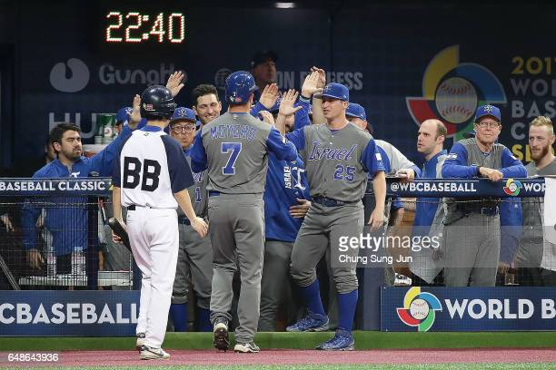 Mike Meyers of Israel celebrates with his teammates after scoring in the tenth inning of the World Baseball Classic Pool A Game One between Israel...