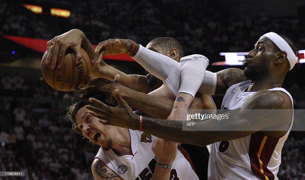 Mike Miller (L) and LeBron James (R) of the Miami Heat vie for a rebound with Tim Duncan (C) of the San Antonio Spurs during the first half in Game 6 of the NBA Finals at the American Airlines Arena June 19, 2013 in Miami, Florida. AFP PHOTO / Brendan SMIALOWSKI