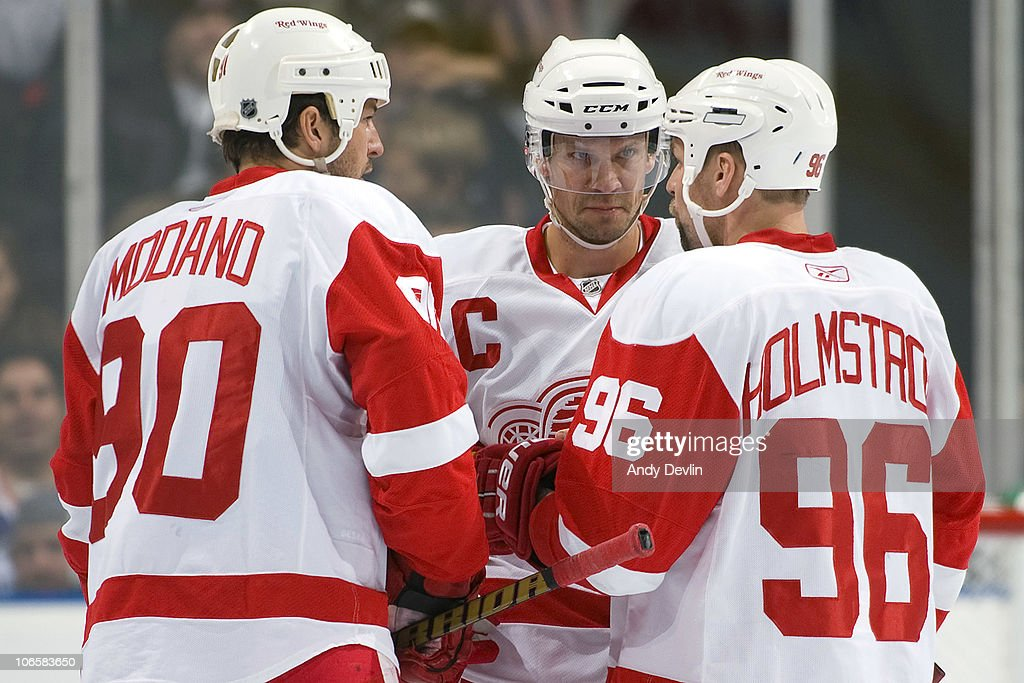 Mike Modano #90, Nicklas Lidstrom #5 and Tomas Holmstrom #96 of the Detroit Red Wings discuss strategy during a stoppage of play against the Edmonton Oilers at Rexall Place on November 5, 2010 in Edmonton, Alberta, Canada.