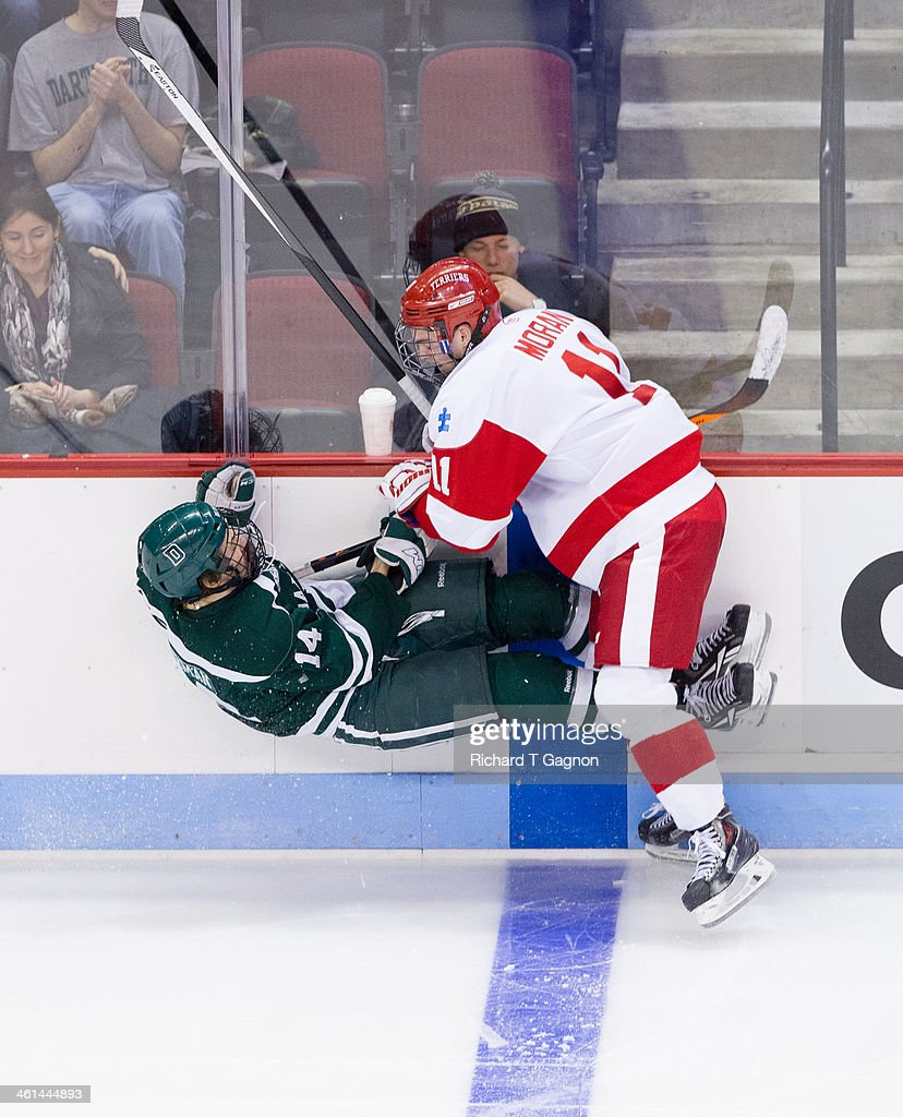 Mike Moran #11 of the Boston University Terriers checks Grant Opperman #14 of the Dartmouth College Big Green into the boards during NCAA hockey action at Agganis Arena on January 8, 2014 in Boston, Massachusetts.