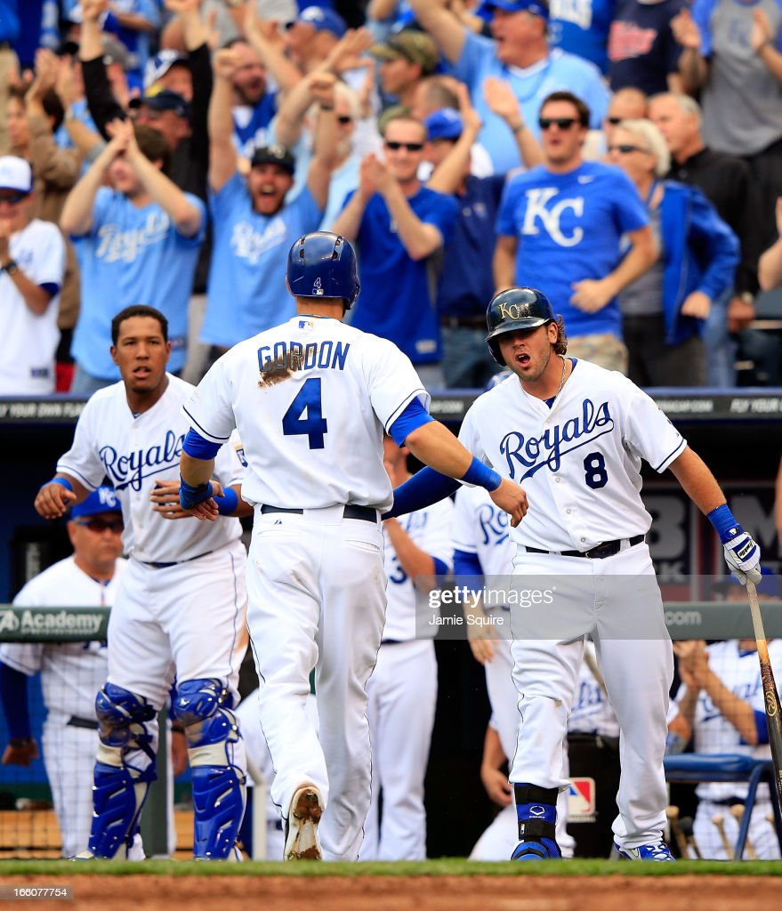 <a gi-track='captionPersonalityLinkClicked' href=/galleries/search?phrase=Mike+Moustakas&family=editorial&specificpeople=6780077 ng-click='$event.stopPropagation()'>Mike Moustakas</a> #8 and Salvador Perez #13 of the Kansas City Royals congratulate <a gi-track='captionPersonalityLinkClicked' href=/galleries/search?phrase=Alex+Gordon+-+Baseball+Player&family=editorial&specificpeople=4494252 ng-click='$event.stopPropagation()'>Alex Gordon</a> #4 after Gordon crossed the plate for a run to make the score 2-1 during the 8th inning of the Kansas City Royals home opener against the Minnesota Twins at Kauffman Stadium on April 8, 2013 in Kansas City, Missouri.