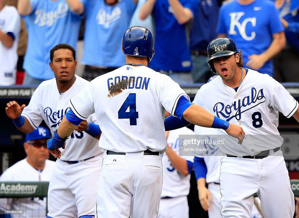 Mike Moustakas #8 and Salvador Perez #13 of the Kansas City Royals congratulate Alex Gordon #4 after Gordon crossed the plate for a run to make the score 2-1 during the 8th inning of the Kansas City Royals home opener against the Minnesota Twins at Kauffman Stadium on April 8, 2013 in Kansas City, Missouri.
