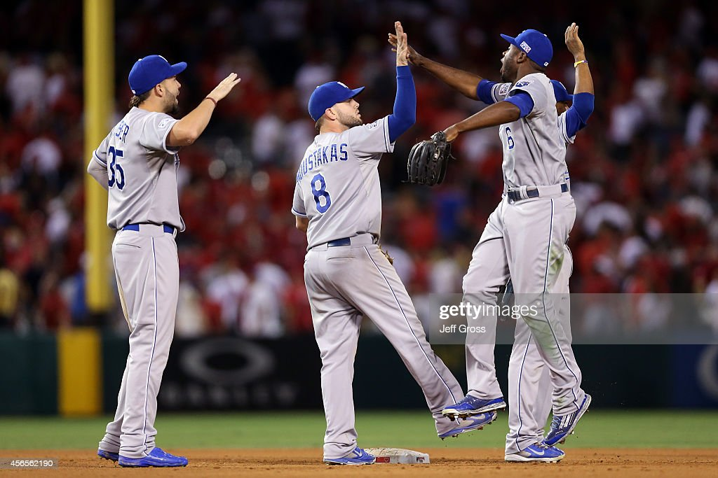 Mike Moustakas #8 celebrates with Lorenzo Cain #6 of the Kansas City Royals after defeating the Los Angeles Angels 3-2 in eleven innings in Game One of the American League Division Series at Angel Stadium of Anaheim on October 2, 2014 in Anaheim, California.