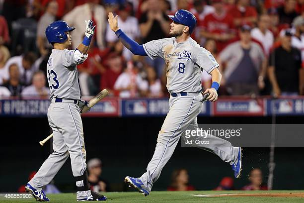 Mike Moustakas celebrates with Norichika Aoki of the Kansas City Royals after scoring in the third inning against the Los Angeles Angels during Game...