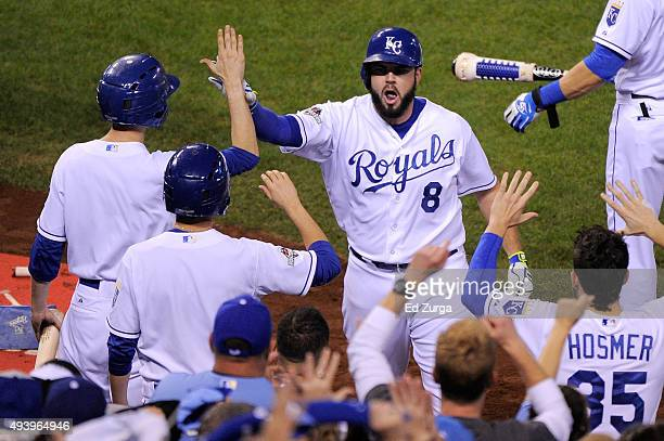 Mike Moustakas of the Kansas City Royals celebrates in the dugout after hitting a solo home run in the second inning against the Toronto Blue Jays in...