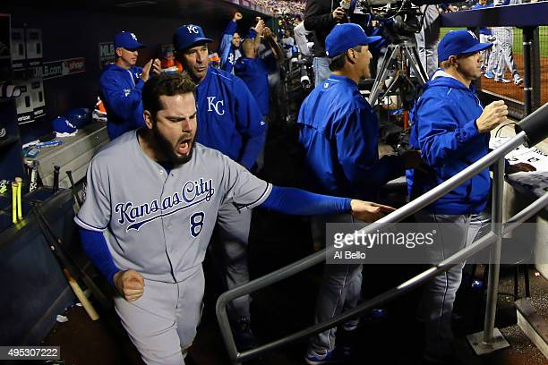 Mike Moustakas of the Kansas City Royals celebrates in the dugout after Eric Hosmer of the Kansas City Royals scores a run off of a grounded out hit...