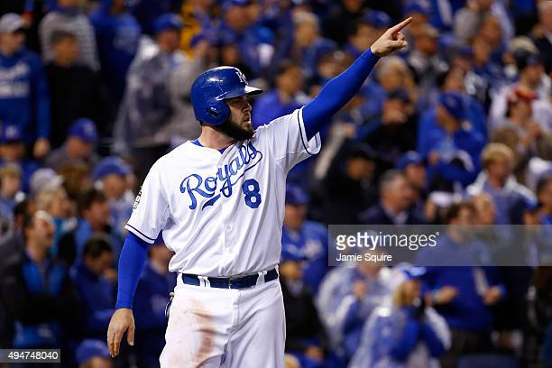 Mike Moustakas of the Kansas City Royals celebrates scoring a run on an RBI double hit by Alex Gordon of the Kansas City Royals in the eighth inning...