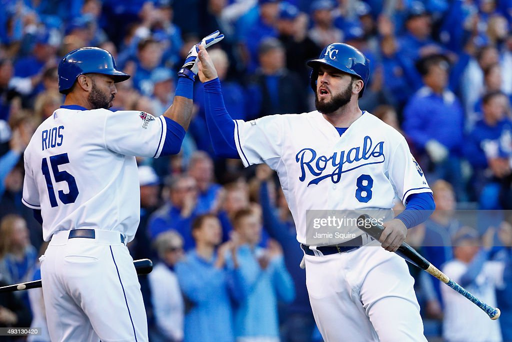 Mike Moustakas #8 of the Kansas City Royals celebrates with Alex Rios #15 of the Kansas City Royals after scoring a run in the seventh inning against the Toronto Blue Jays in game two of the American League Championship Series at Kauffman Stadium on October 17, 2015 in Kansas City, Missouri.