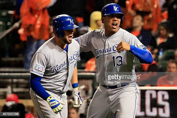 Mike Moustakas of the Kansas City Royals celebrates with teammate Salvador Perez of the Kansas City Royals after hitting a two run home run to right...