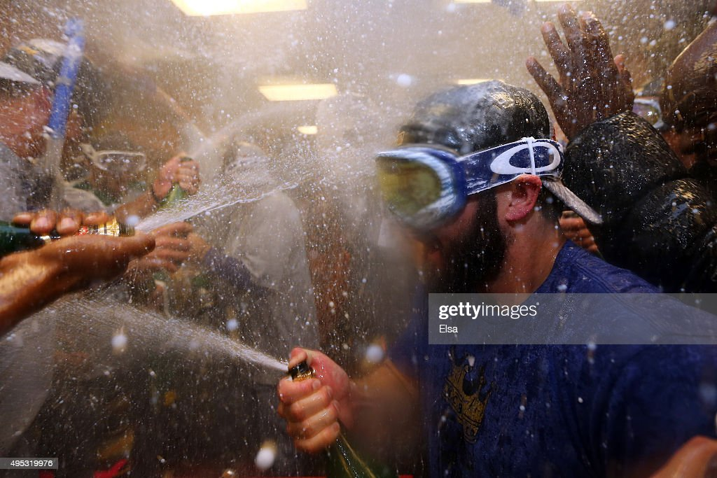Mike Moustakas #8 of the Kansas City Royals celebrates with teammates in the clubhouse after defeating the New York Mets to win Game Five of the 2015 World Series at Citi Field on November 1, 2015 in the Flushing neighborhood of the Queens borough of New York City. The Kansas City Royals defeated the New York Mets with a score of 7 to 2 to win the World Series.