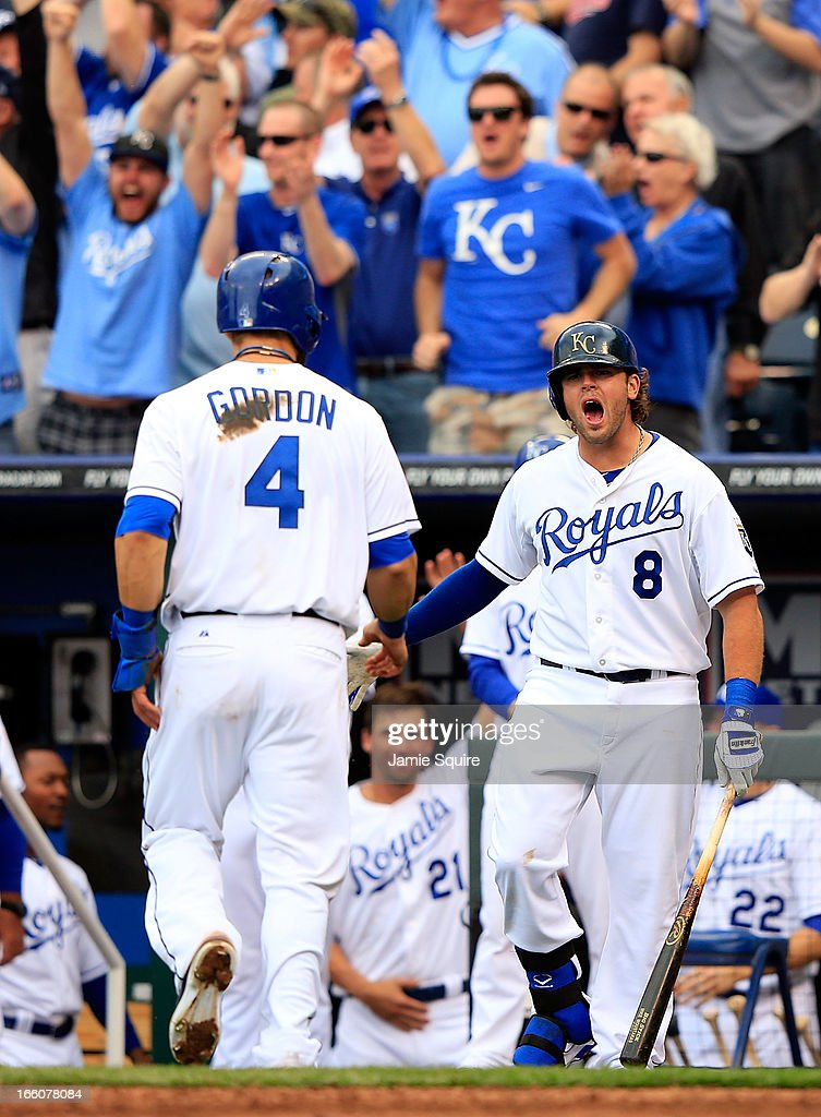 <a gi-track='captionPersonalityLinkClicked' href=/galleries/search?phrase=Mike+Moustakas&family=editorial&specificpeople=6780077 ng-click='$event.stopPropagation()'>Mike Moustakas</a> #8 of the Kansas City Royals congratulates <a gi-track='captionPersonalityLinkClicked' href=/galleries/search?phrase=Alex+Gordon+-+Baseball+Player&family=editorial&specificpeople=4494252 ng-click='$event.stopPropagation()'>Alex Gordon</a> #4 after Gordon crossed the plate for a run to make the score 2-1 during the 8th inning of the Kansas City Royals home opener against the Minnesota Twins at Kauffman Stadium on April 8, 2013 in Kansas City, Missouri.
