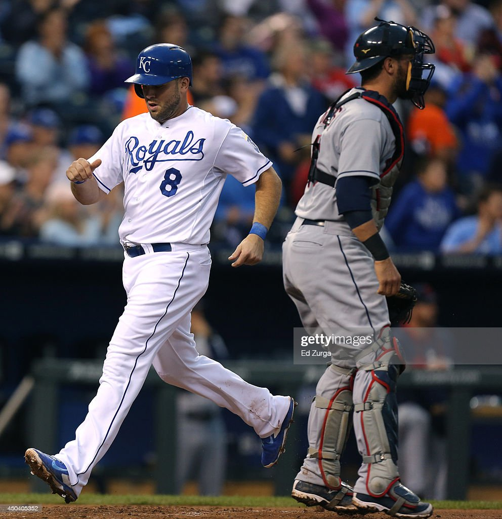 Mike Moustakas #8 of the Kansas City Royals crosses home past Yan Gomes #10 of the Cleveland Indians as he scores on a Omar Infante single in the third inning at Kauffman Stadium on June 10, 2014 in Kansas City, Missouri.