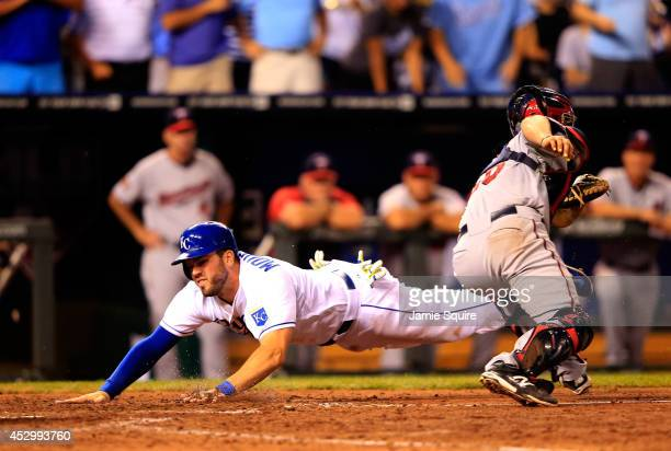 Mike Moustakas of the Kansas City Royals dives for the plate to score as Eric Fryer of the Minnesota Twins is late applying the tag during the 7th...