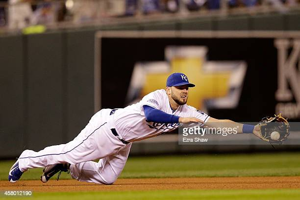 Mike Moustakas of the Kansas City Royals dives to make a catch in the fourth inning against the San Francisco Giants during Game Six of the 2014...