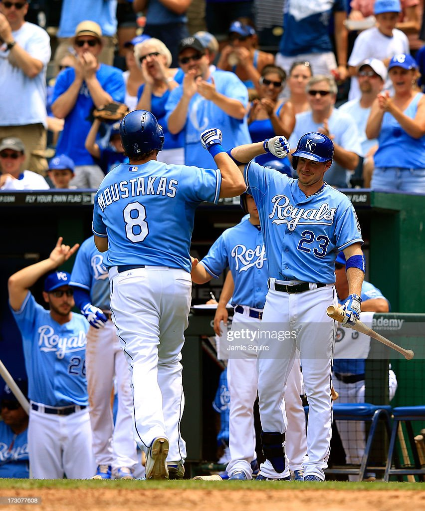 <a gi-track='captionPersonalityLinkClicked' href=/galleries/search?phrase=Mike+Moustakas&family=editorial&specificpeople=6780077 ng-click='$event.stopPropagation()'>Mike Moustakas</a> #8 of the Kansas City Royals is congratualted by <a gi-track='captionPersonalityLinkClicked' href=/galleries/search?phrase=Elliot+Johnson+-+Baseball+Player&family=editorial&specificpeople=4175454 ng-click='$event.stopPropagation()'>Elliot Johnson</a> #23 after hitting a solo home run during the 4th inning of the game against the Oakland Athletics at Kauffman Stadium on July 6, 2013 in Kansas City, Missouri.