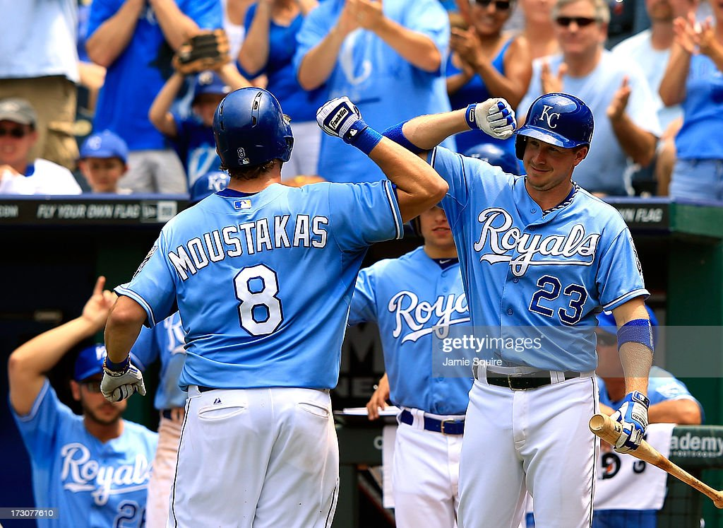 <a gi-track='captionPersonalityLinkClicked' href=/galleries/search?phrase=Mike+Moustakas&family=editorial&specificpeople=6780077 ng-click='$event.stopPropagation()'>Mike Moustakas</a> #8 of the Kansas City Royals is congratualted by <a gi-track='captionPersonalityLinkClicked' href=/galleries/search?phrase=Elliot+Johnson&family=editorial&specificpeople=4175454 ng-click='$event.stopPropagation()'>Elliot Johnson</a> #23 after hitting a solo home run during the 4th inning of the game against the Oakland Athletics at Kauffman Stadium on July 6, 2013 in Kansas City, Missouri.