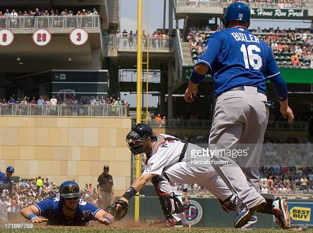 Mike Moustakas of the Kansas City Royals is safe as Joe Mauer of the Minnesota Twins defends home plate and Billy Butler of the Kansas City Royals...