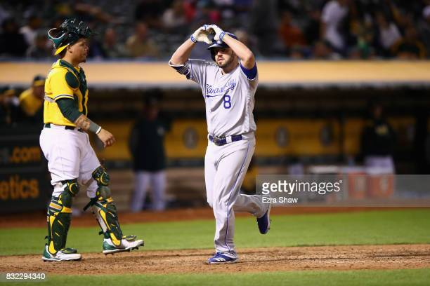 Mike Moustakas of the Kansas City Royals reacts in front of Bruce Maxwell of the Oakland Athletics after he hit a home run in the eighth inning at...