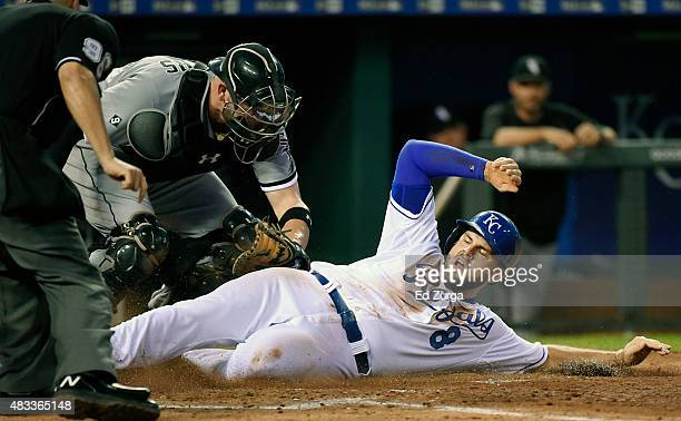 Mike Moustakas of the Kansas City Royals slides into home to score against Tyler Flowers of the Chicago White Sox in the fifth inning at Kauffman...
