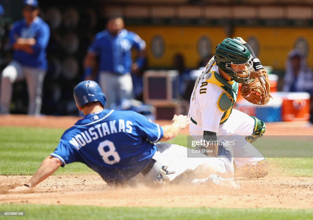 Mike Moustakas #8 of the Kansas City Royals slides safely into home plate past catcher Dustin Garneau #12 of the Oakland Athletics to score in the fifth inning at Oakland Alameda Coliseum on August 16, 2017 in Oakland, California.