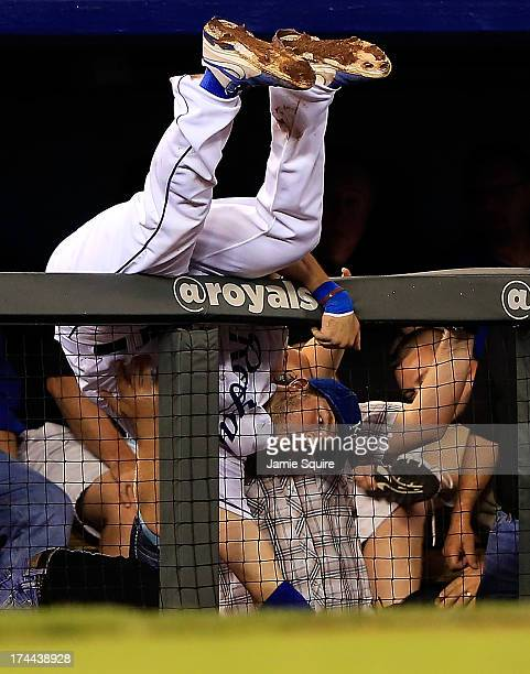 Mike Moustakas of the Kansas City Royals tumbles over a railing while chasing a foul ball hit by Nick Markakis of the Baltimore Orioles during the...