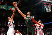 Mike Muscala of the Atlanta Hawks defends as Thabo Sefolosha battles for a rebound against Zaza Pachulia of the Milwaukee Bucks at Philips Arena on...