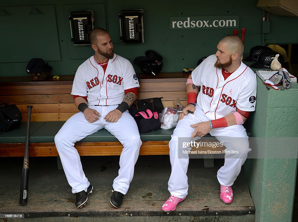 Mike Napoli #12 and Jonny Gomes #5 of the Boston Red Sox talk in the dugout before a game against the Toronto Blue Jays on May 12, 2013 at Fenway Park in Boston, Massachusetts.