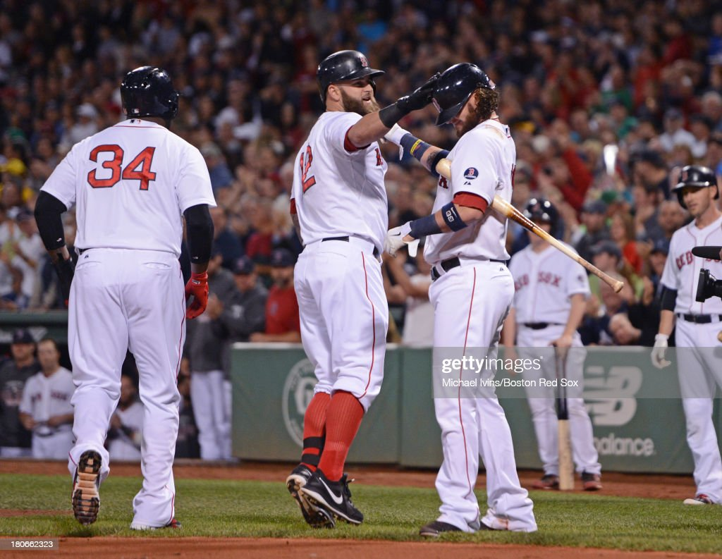 Mike Napoli #12 of the Boston Red Sox celebrates after hitting a two-run home run against the New York Yankees with David Ortiz #34 and Jarrod Saltalamacchia #39 the first inning on September 15, 2013 at Fenway Park in Boston Massachusetts.